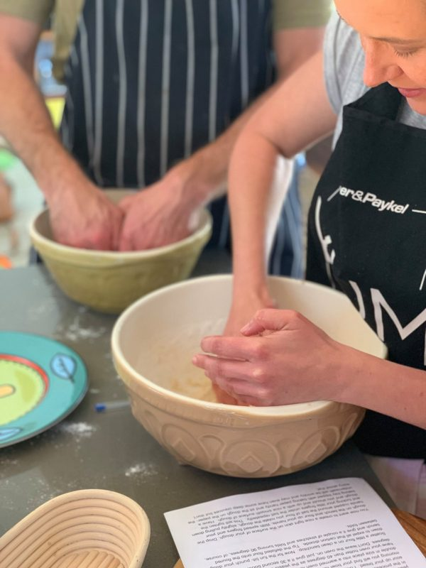 Close up of people kneading dough in a bowl