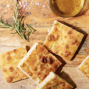 Baked focaccia bread served with olives. Traditional Italian Focaccia with rosemary over dark texture background. Top view, flat lay.